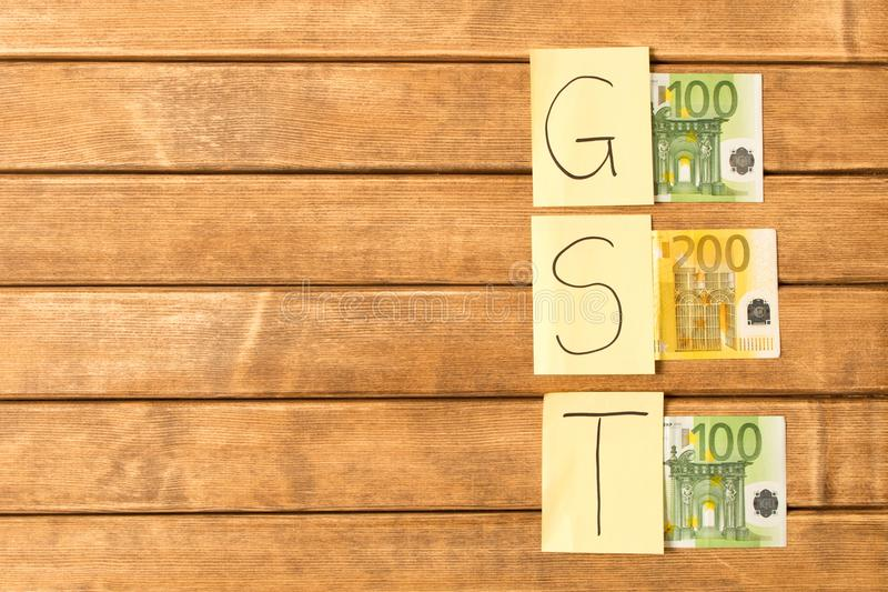 Goods and Services Tax . GST inscription with banknotes on wooden background royalty free stock photography