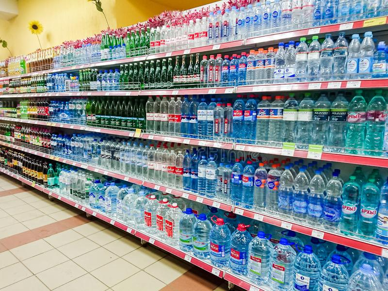 Goods on the shelf of a grocery store. Water and various soft drinks in plastic and glass bottles. stock photo