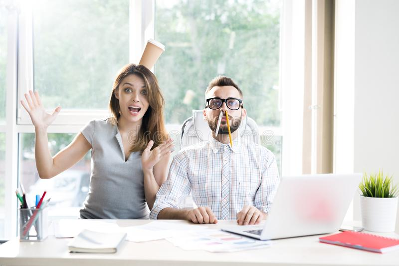 Goofy Business Entrepreneurs. Portrait of two modern business people goofing around having fun while looking at camera sitting at desk in sunlit office royalty free stock images