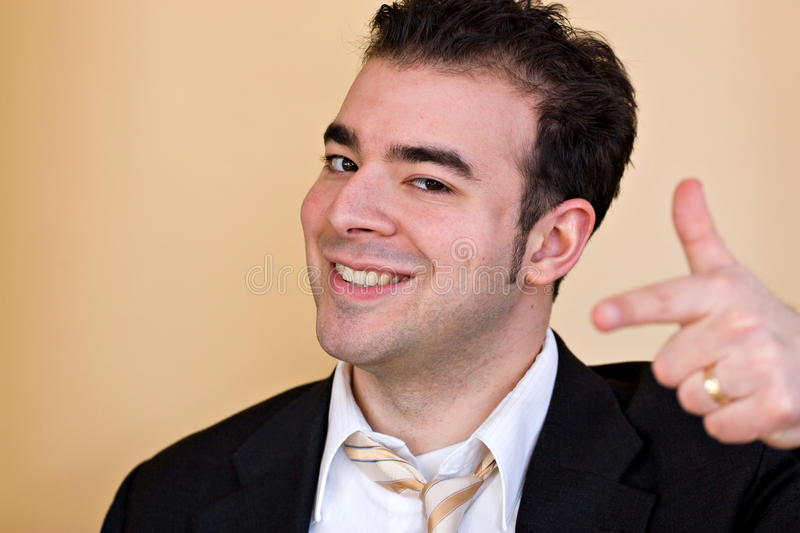 Goofy Business Man. A goofy smiling business man pointing and trying to act like he is a cool guy. Shallow depth of field with focus on the face stock images