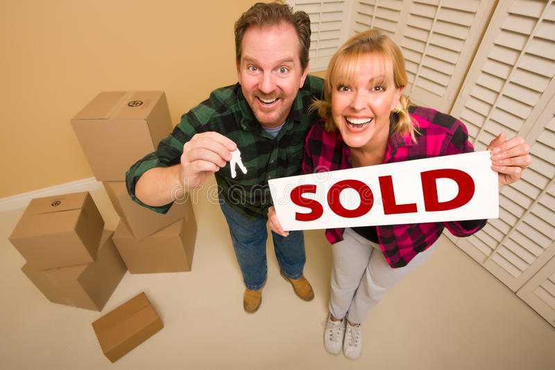 Goofy Couple Holding Keys and Sold Sign Boxes Near. Goofy Couple Holding Key and Sold Sign in Room with Packed Cardboard Boxes stock photography