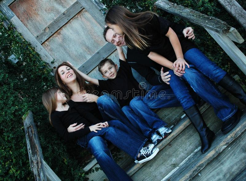 Goofy Family Portrait. Up-close view of American family in black shirts and denim, blue jean pants. Family of five being goofy during a family portrait. Casual stock photos