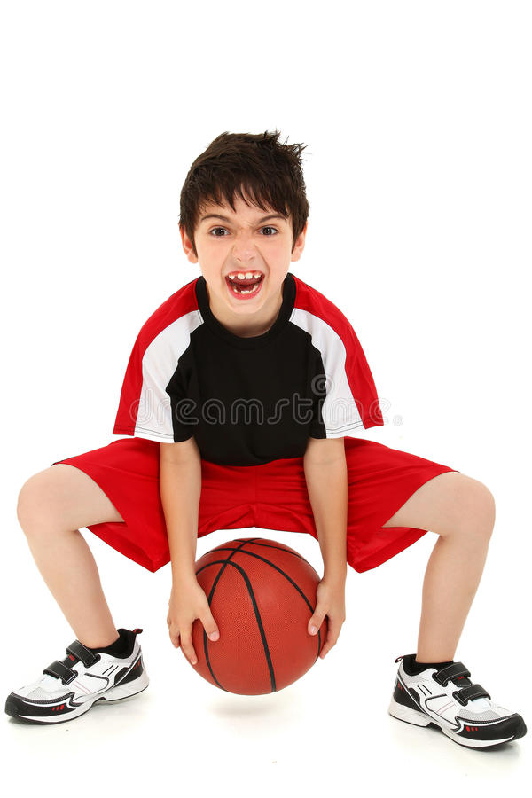 Goofy Funny Boy Child Basketball Player. Team sport basketball player child with ball making crazy expressions royalty free stock images