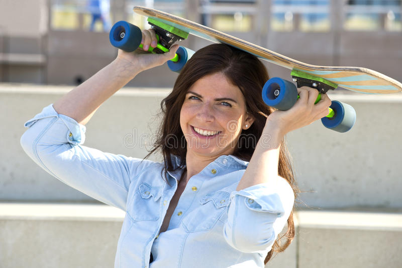 Goofy girl with skateboard. Goofy girl holding a skateboard on her head royalty free stock photo