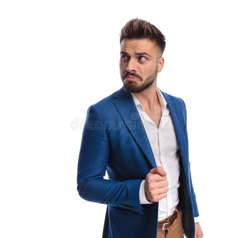 Goofy man looking away with hand on lounge jacket. Goofy man in suit looking away with hand on lounge jacket on white background stock image