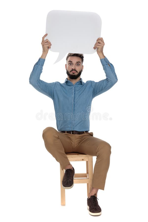 Goofy man sitting with an empty message bubble up. Goofy man in blue jeans shirt sitting with an empty message bubble up in the air on white background royalty free stock photos