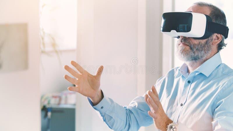 Googlar för virtuell verklighet för man för mogen affär bärande/VR exponeringsglas royaltyfria bilder