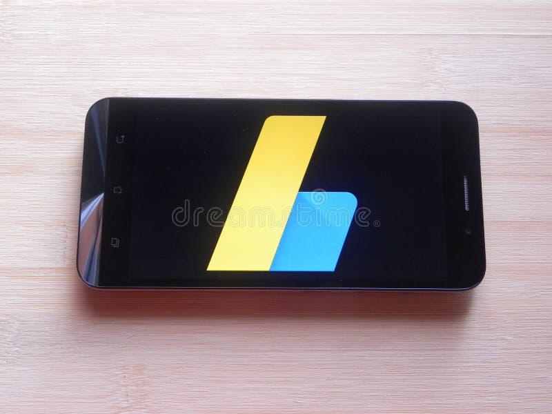Google AdSense app. On smartphone kept on wooden table stock image