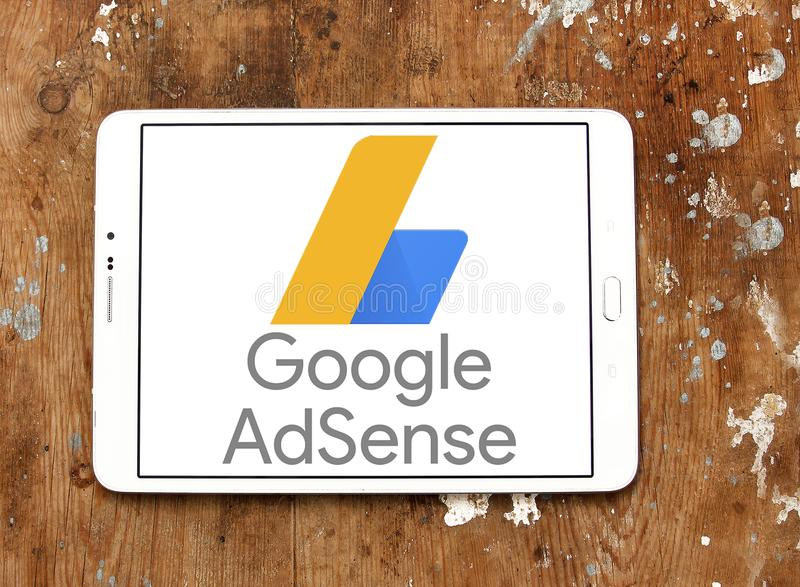 Google AdSense logo. Logo of Google AdSense on samsung tablet on wooden background . Google AdSense is a program run by Google that allows publishers in the stock images