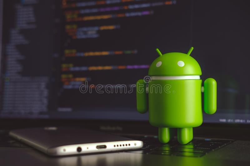 Google Android figure standing on laptop keyboard royalty free stock images
