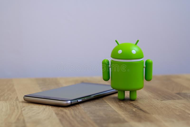 Google Android figure standing next to smart phone. New York, USA - July 2, 2018 - Google Android figure standing next to smart phone royalty free stock image