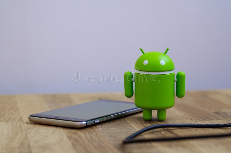 Google Android figure standing next to smart phone royalty free stock photos