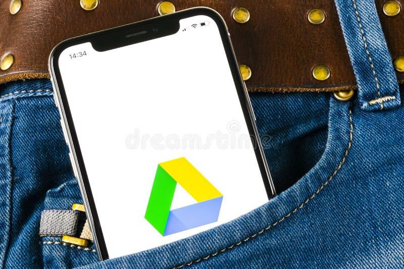 Google conduisent l'icône d'application sur l'écran de l'iPhone X d'Apple dans la poche de jeans Google conduisent l'icône Google photographie stock libre de droits