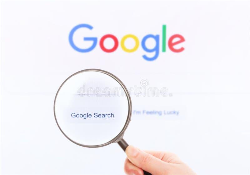 Google-Homepage auf dem Bildschirm unter einer Lupe lizenzfreies stockbild