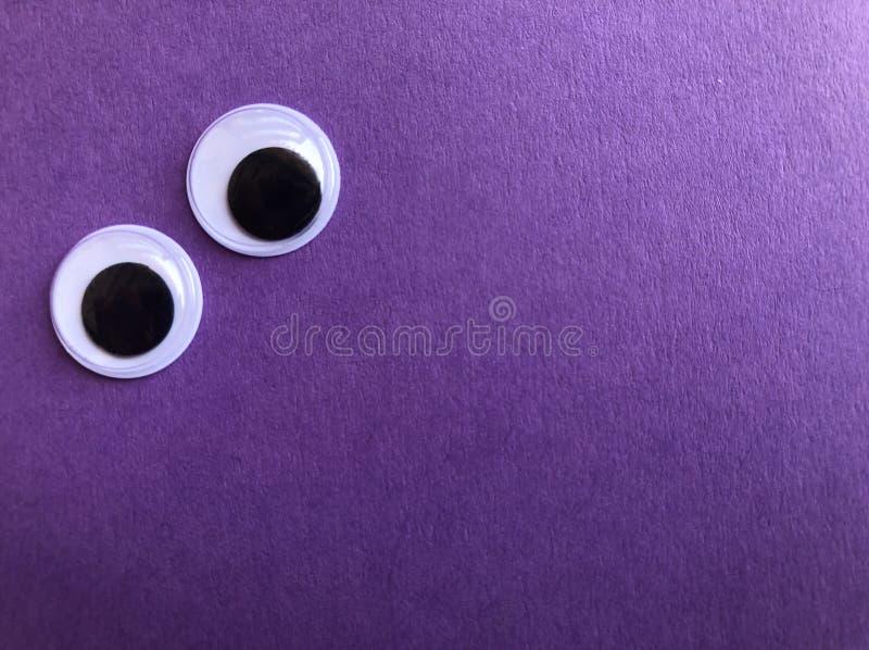 Googly ögon på purpurfärgad bakgrund med kopieringsutrymme arkivfoto