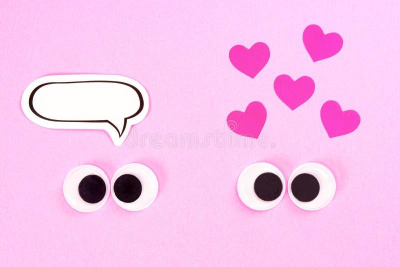 Googly Augen Merkwürdige Paare der schielenden Liebhaber auf rosafarbenem Hintergrund mit etwas kleinen Herzen und Kopienraum für stockbilder