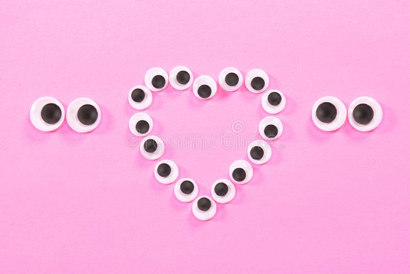 Googly Augen Merkwürdige Augen von Paaren Liebhabern auf rosafarbenem Hintergrund Mit einem Herzzeichen durchschnittlich lizenzfreies stockbild