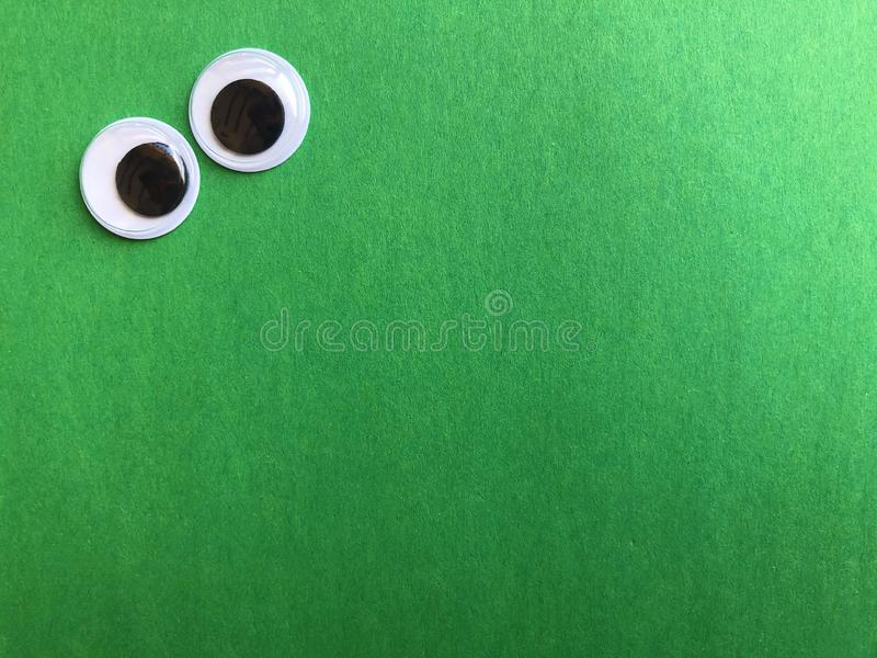 Googly eyes on green background with copy space. Googly eyes on green textured background with room for text or image royalty free stock images