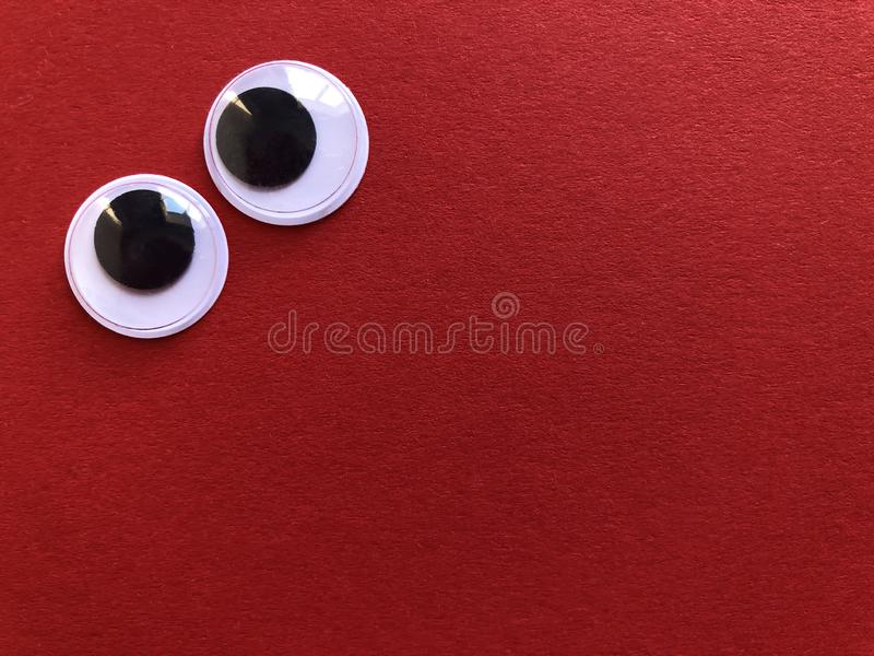 Creative fun background, googly eyes. Googly eyes isolated on a plain red background with copy space stock photo