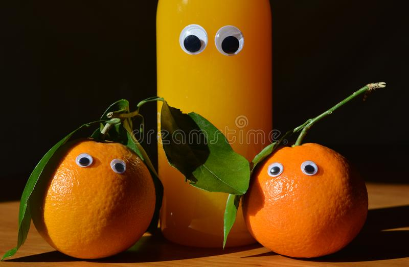 Googly eyes oranges and orange juice. Creative fun food concept. Creative fun food photography. Two fresh oranges with googly eyes and a googly eyed bottle of stock images