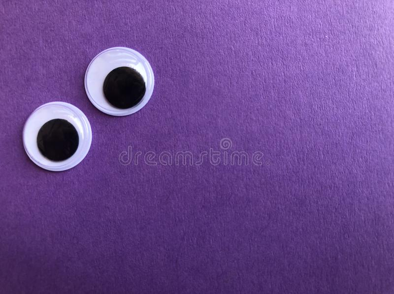 Googly eyes on purple background with copy space. Googly eyes on purple textured background with room for text or image stock photo