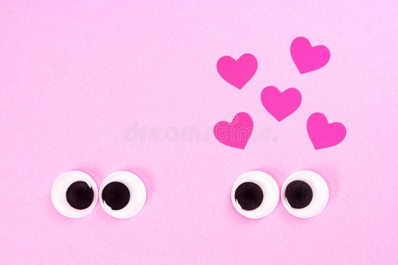 Googly eyes of strange pair of lovers, one of which cross-eyed, on rose background with some small hearts. Close up toy. Googly eyes of strange pair of lovers royalty free stock photography