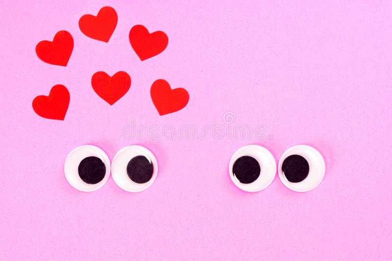 Googly eyes of strange pair of lovers on rose background with some small hearts. Close up toy eyes. Googly eyes of strange pair of lovers on rose background royalty free stock images