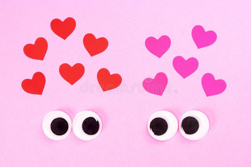 Googly eyes of strange pair of lovers on rose background with some small hearts. Close up toy eyes. Googly eyes of strange pair of lovers on rose background royalty free stock photo
