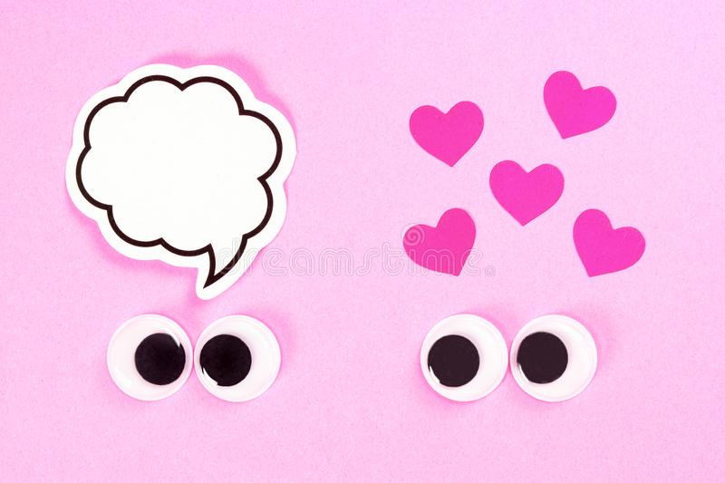 Googly eyes of strange pair of lovers on rose background with some small hearts and copy space for thoughts. Close up. Googly eyes of strange pair of lovers on stock photography