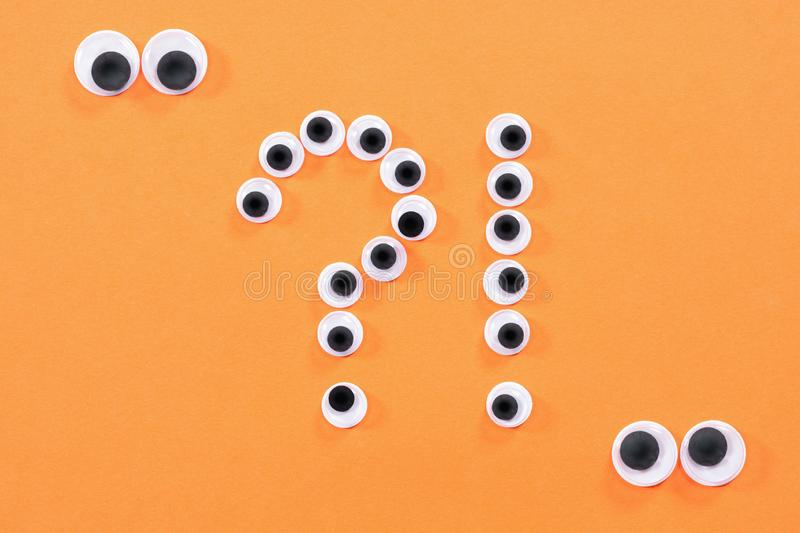 Googly eyes. Two strange persons with mad eyes look at some crazy toy eyes on orange background in the shape of question. Googly eyes. Two strange persons with royalty free stock photos