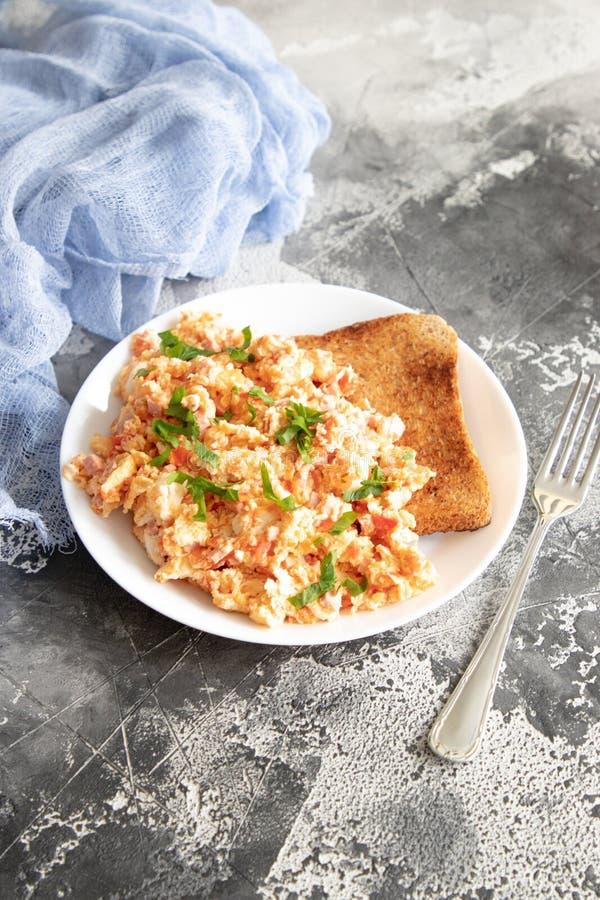 Gooi eieren met tomaat en peterselie door elkaar royalty-vrije stock afbeeldingen