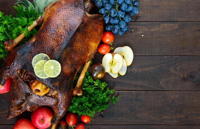 Goose baked in the oven with apples and grapes. Christmas goose on a wooden background royalty free stock image