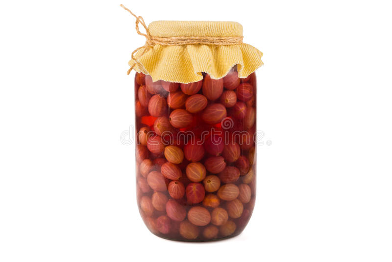 Gooseberry compote. Jar of canned gooseberry compote on a white background royalty free stock photo