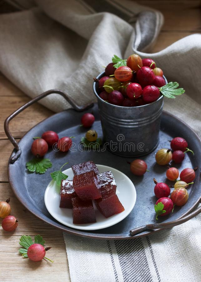 Gooseberry marmalade cubes and gooseberries on a tin tray. Rustic style. Selective focus stock images