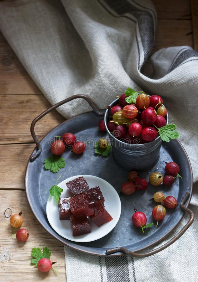Gooseberry marmalade cubes and gooseberries on a tin tray. Rustic style. Selective focus royalty free stock images