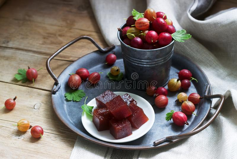 Gooseberry marmalade cubes and gooseberries on a tin tray. Rustic style. Selective focus royalty free stock image