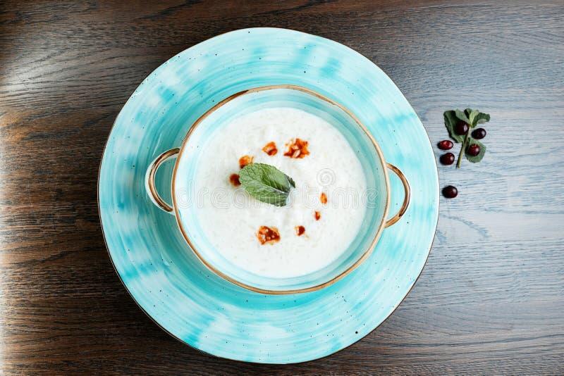 Gorąca kremowa polewka z zieleniami w błękitnym pucharze na rocznika stole w restauracyjnej porcji orientalnej kuchni fotografia royalty free