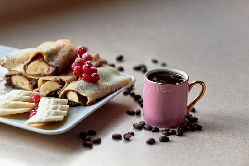 Gorący bliny z czekolada bananem i rozszerzaniem się Dekorujący z rodzynkami słodki deser Następnie będzie filiżanka kawy zdjęcia royalty free
