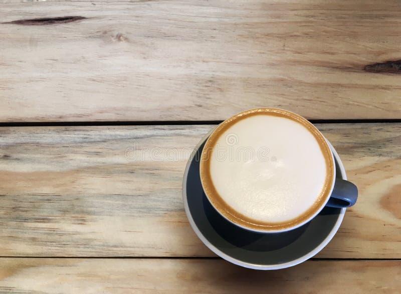 Gorąca cappuccino kawa w błękitnej filiżance na drewnianym stołowym tle Sztuka mleko piany okręgu kształt z kopii przestrzenią obraz royalty free