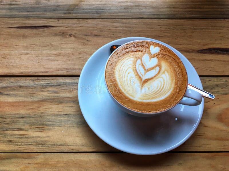 Gorąca cappuccino kawa w białym spodeczku z łyżką na drewnianym stołowym tle i filiżance Sztuka mleko piany rysunek zdjęcia stock