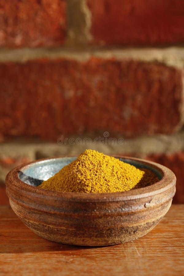 Gorąca curry'ego proszka pikantność w pucharze na drewnianym stole zdjęcia royalty free