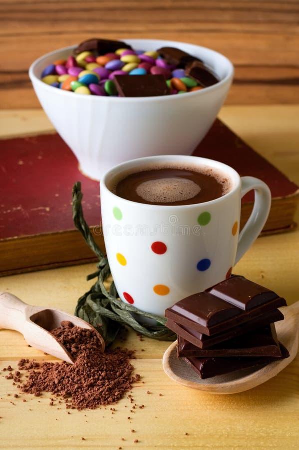 Gorąca czekolada w łaciastej filiżance z cukierkami w pucharze zdjęcie stock