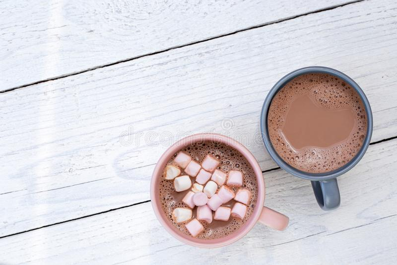 Gorąca czekolada w dwa kubkach, jeden z małymi marshmallows, odizolowywającymi na bielu malował drewno z góry Przestrze? dla teks obrazy stock