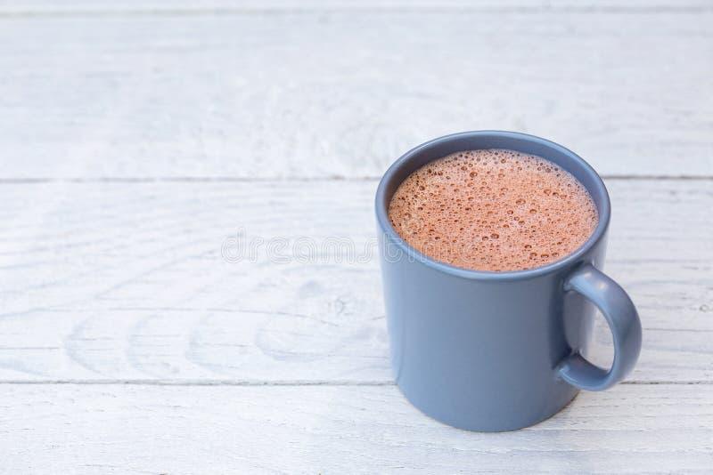 Gorąca czekolada w niebieskoszarym ceramicznym kubku na bielu malował drewno Przestrze? dla teksta obrazy royalty free