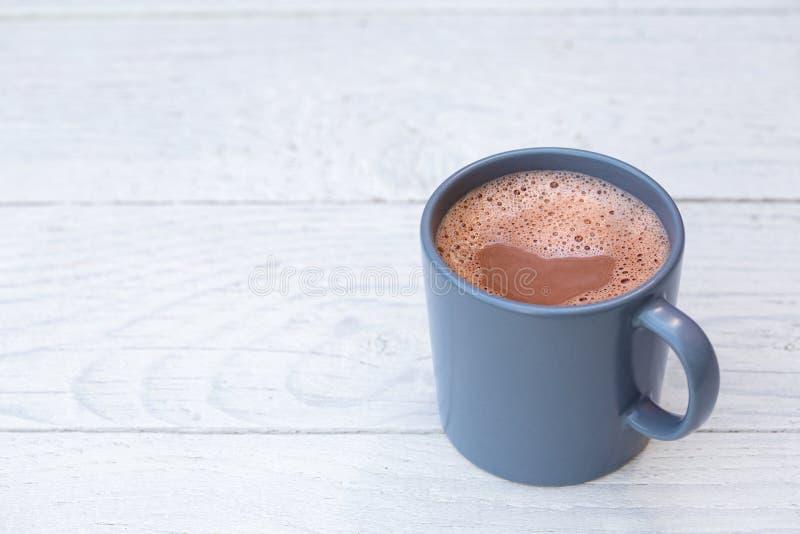 Gorąca czekolada w niebieskoszarym ceramicznym kubku na bielu malował drewno Przestrze? dla teksta obraz royalty free