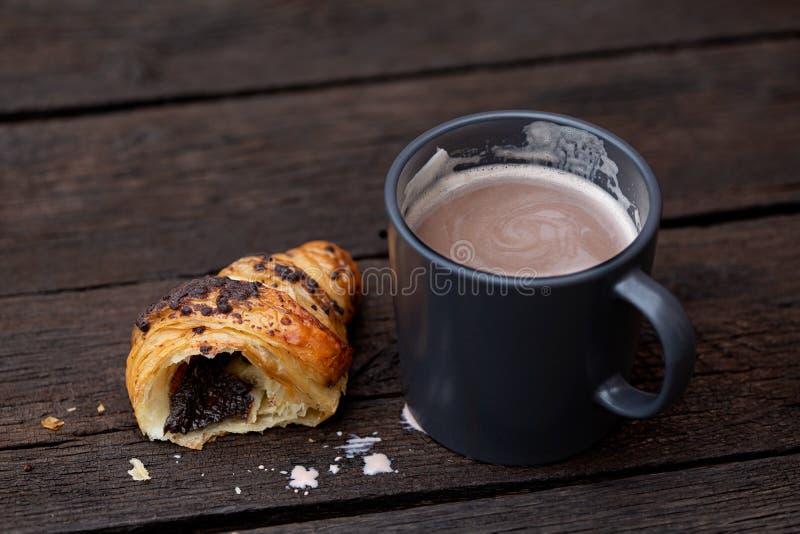 Gorąca czekolada w niebieskoszarym ceramicznym kubku obok połówki odizolowywającej na nieociosanym ciemnego brązu drewna stole cz obraz royalty free