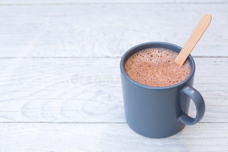 Gorąca czekolada w niebieskoszarym ceramicznym kubku z drewnianą kociubą na bielu malował drewno Przestrze? dla teksta zdjęcia royalty free