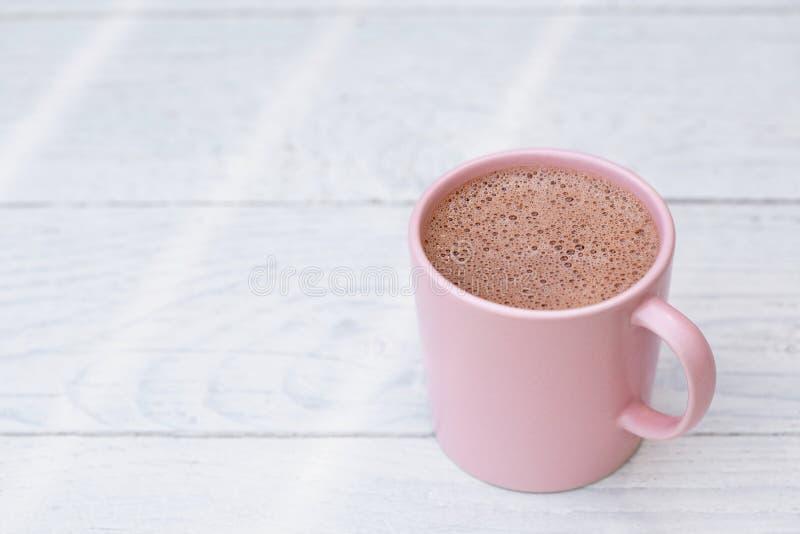 Gorąca czekolada w różowym ceramicznym kubku na bielu malował drewno Przestrze? dla teksta obrazy stock