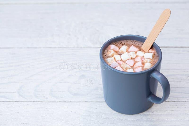 Gorąca czekolada z małymi marshmallows i drewnianą kociubą w niebieskoszarym ceramicznym kubku na bielu malował drewno Przestrze? zdjęcia royalty free