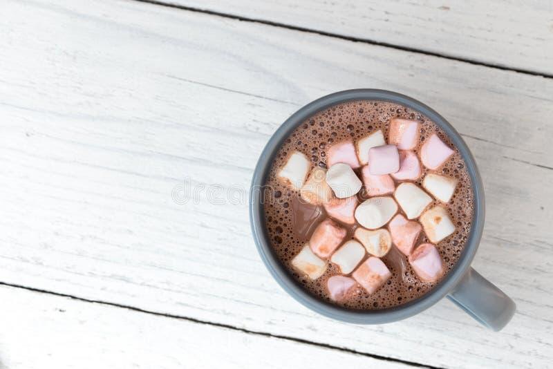 Gorąca czekolada z małymi marshmallows w niebieskoszarym ceramicznym kubku odizolowywającym na bielu malował drewno z góry Przest fotografia royalty free